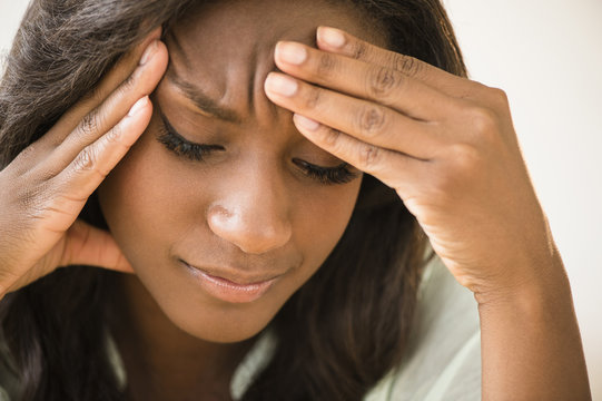 Black woman frowning with head in hands