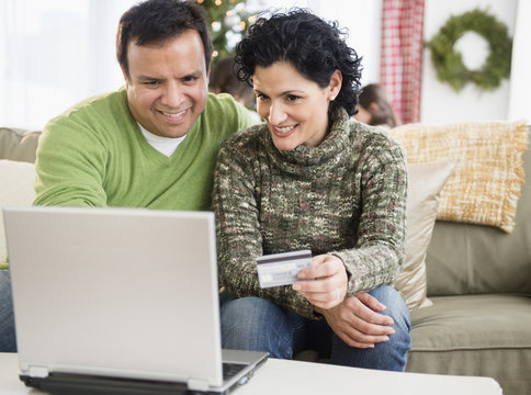 Couple shopping online in living room