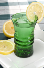 Green Glass with Lemons and Plaid Background