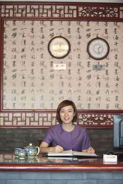 Chinese receptionist at hotel front desk