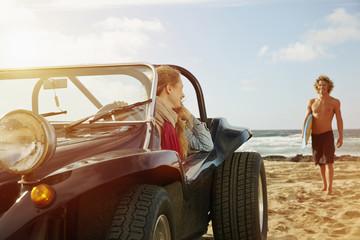 Caucasian woman sitting in jeep on beach