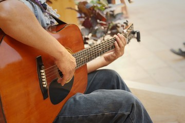 The guitarist player sitting at the park.