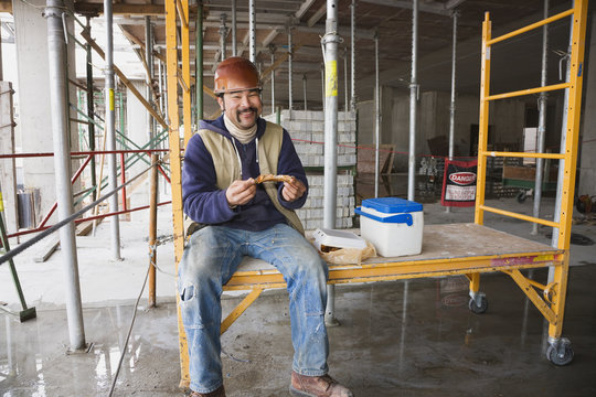 Mixed race construction worker eating lunch