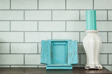 picture frame and vintage candlestick on brick wall