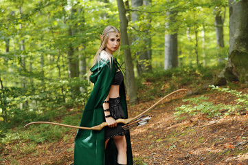 female elf with a bow in the forest