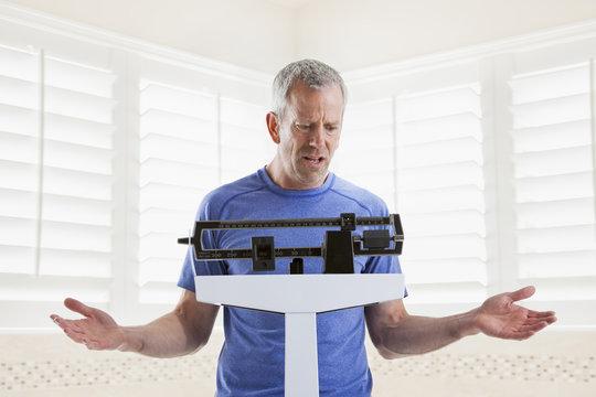 Caucasian man weighing himself