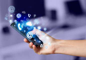 Business man holding smart phone with media icons