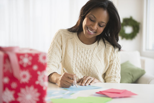 African American woman writing at desk