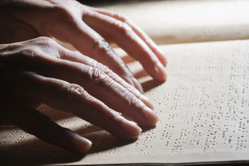 Close up of Hispanic person reading Braille
