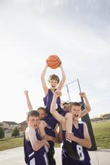 Caucasian basketball team cheering on court