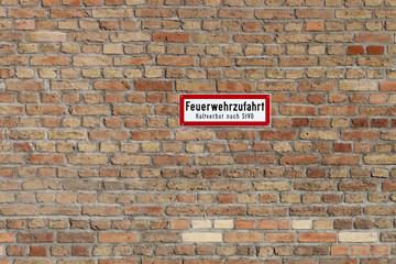 Backsteinwand mit Feuerwehrschild
