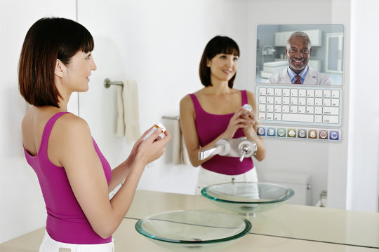 Mixed race woman using computer in mirror