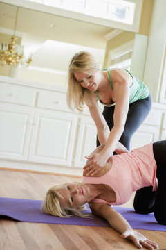 Caucasian woman working with yoga instructor in home