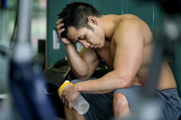 Pacific Islander man resting in gym