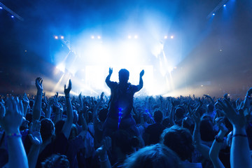 crowd of people at concert in front of the stage with lights