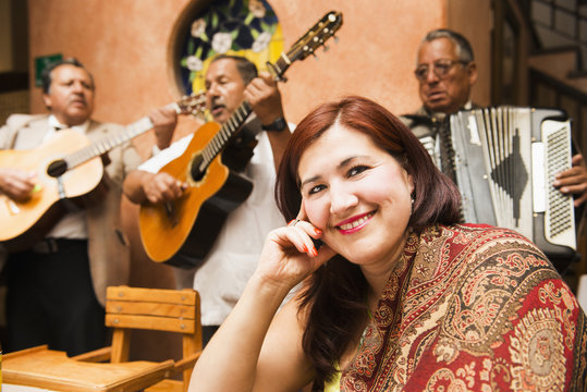 Hispanic woman in restaurant with Mariachi band