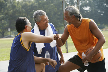 Multi-ethnic men laughing on basketball court