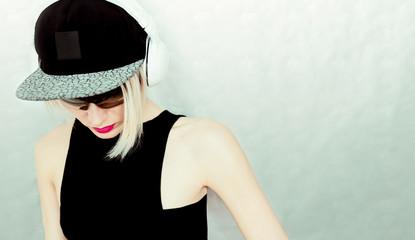 DJ girl in cap and stylish headphones