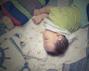 Cute Asian baby boy sleeping and drinking milk