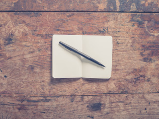 Pen and notepad on wooden table
