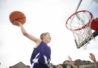 Boy dunking basketball in hoop