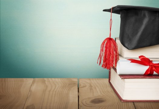 Scroll. A graduation mortarboard on top of a stack of books