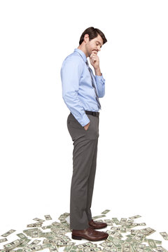 Caucasian businessman standing on money
