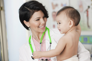 Doctor holding smiling baby in doctor's office