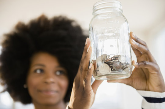 Mixed race woman holding jar of change