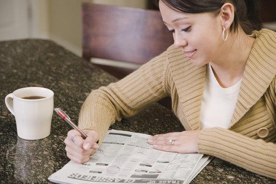 Hispanic woman searching newspaper classified ads