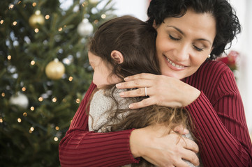 Mother and daughter hugging by Christmas tree