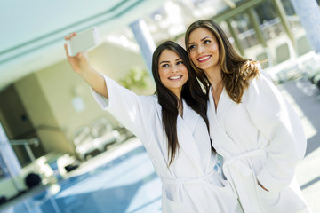 Two attractive ladies taking a selfie next to a swimming pool