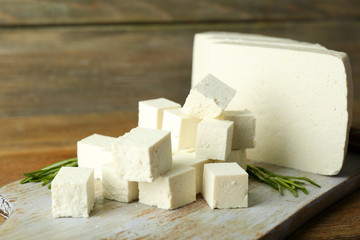 Sliced feta cheese with rosemary on table on wooden background