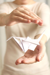 Closeup of female hands with paper crane