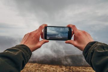 Hiker taking photographs mystery fog