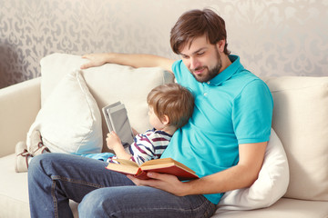 Father and son read a book or tablet
