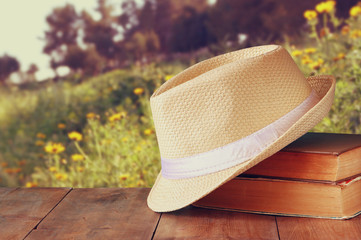 fedora hat and stack of books over wooden table and floral natur