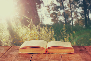 open book over wooden rustic table in front of wild landscape an