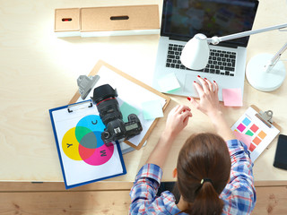 Female photographer sitting on the desk with laptop