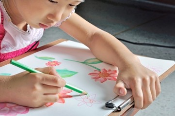 little Asian girl draws flower picture by colour pencil