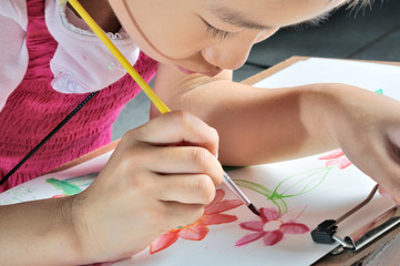 little Asian girl hand paint with her watercolor picture
