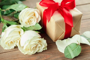 Day. Red roses and holiday gift on a wooden table