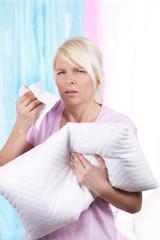 Frau mit Bettzeug und Hausstaub Allergie