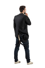 Rear view of young bearded artist looking at blank wall