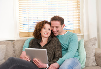 Happy couple sitting on couch looking at computer tablet