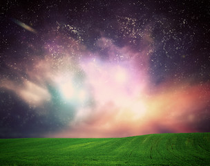 Field of grass under dream galaxy sky, space, glowing stars.