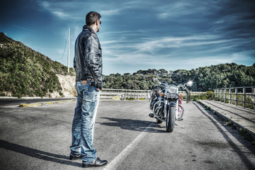 biker standing next to a classic motorcycle