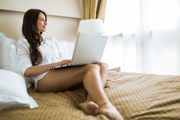 Beautiful woman with sexy long legs in shirt using a notebook