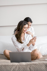 Two beautiful women using a notebook while in bed