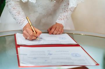 bride signing signature on wedding certificate.